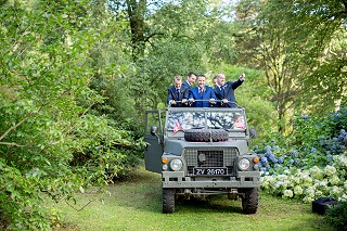 Groom arriving at the woodland wedding ceremony in a military Land Rover Lightweight